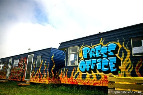 A press office at a festival, with a graffiti sign